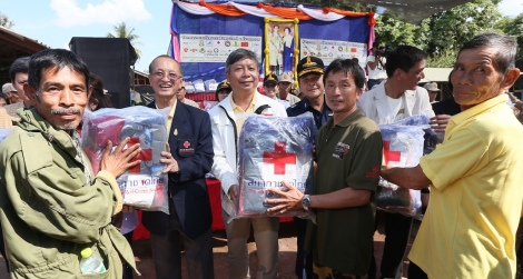 Pairuch Puenduang (centre) of the HKKT Fund committee and Lt. Gen. Dr. Amnat Barlee (second from left), Director of the Relief and Community Health Bureau of the Thai Red Cross Society, hand out relief packages to people affected by the cold in the Mae Suai, Muang, and Wieng Pa Pao districts of Chiang Rai province.