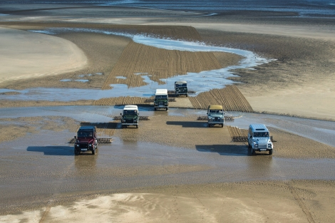 Behind the scenes images showing the making of the 1km drawing in the sand at Red Wharf Bay that required a fleet of six Land Rovers, each towing an agricultural 12-foot harrow, to draw the unmistakable outline of the Defender. The six vehicles chart the evolution of the Defender from its introduction in 1948 to the present day.